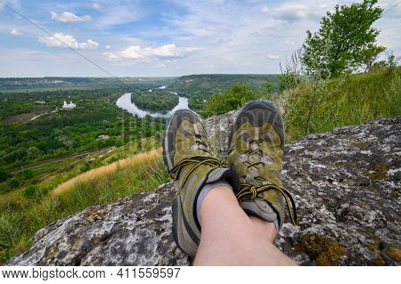 Man's feet in trekking shoes over view to Naslavcha village by the Dniester river, north of Moldova