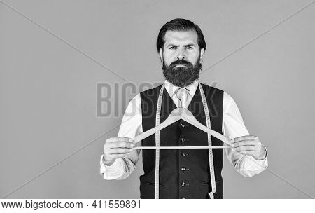 Tailor Man Holds In His Hand A Hanger. Handsome Man In Formal Vest. Wardrobe For Business Fashion. C