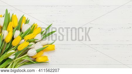 Yellow and white tulip flowers bouquet on wooden background. Top view flat lay. With copy space