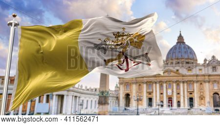 The Flag Of The Vatican City State Fluttering In The Wind With St. Peter\'s Basilica Blurred In The