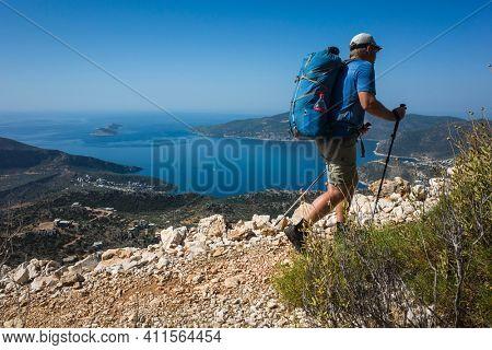 Hiking Lycian way. Man backpacker is trekking on stony path high above Mediterranean sea coast on Lycian Way trail from Kalkan to Bezirgan, Outdoor activity in Turkey