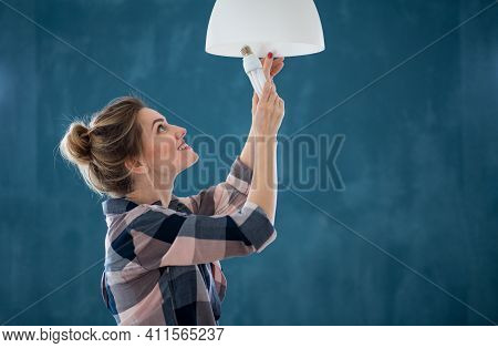 Happy Woman Changing Light Bulb Indoors At Home, Relocation And Diy Concept.