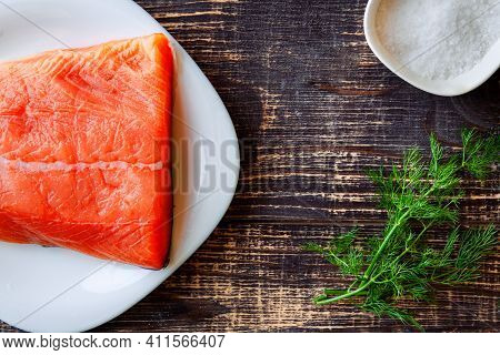 A Piece Of Salted Salmon With Fresh Dill, Next To A Bowl Of Salt On Table