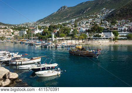 Kalkan, Turkey - 12 October, 2019: Boats in Kalkan Marina and town on hills on Turkish Mediterranean coast, Popular tourist destination
