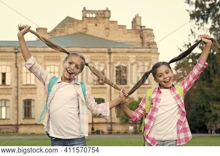 Happy Hair, Happy You. Happy Girls Hold Long Hair Tails. Hair Salon. Beauty Look Of School Children.