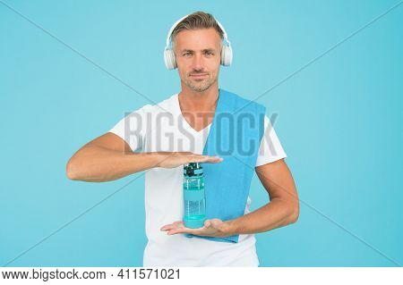 Drinking Water Is Key To Reaching Fitness Goals. Healthy Drinking Habits. Handsome Man In Headphones
