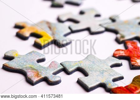 Several Puzzle Pieces On A White Background. Disconnected Pieces Of A Puzzle Game. Macro Shot.