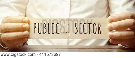 Businessman Puts Together Wooden Puzzles With The Words Public Sector. Enterprises, Organizations An
