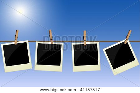 Four Pictures Hanging On Rope Against Bright Sky