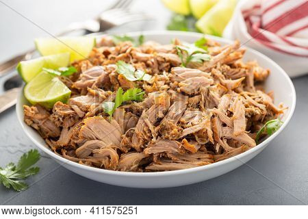 Pork Carnitas In A Bowl With Celery And Lime Wedges
