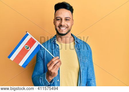 Young arab man holding costa rica flag looking positive and happy standing and smiling with a confident smile showing teeth