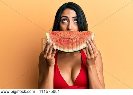 Beautiful hispanic woman putting watermelon slice as funny smile angry and mad screaming frustrated and furious, shouting with anger looking up.