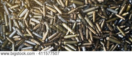 Empty Carbine Or Rifle Cartridges. A Large Number Of Cases. Background Of Brass Ammunition Cartridge