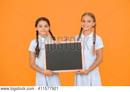 True Information. Little Girls Hold Writing Surface Yellow Background. Children And Chalkboard For W