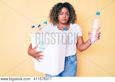 Young african american plus size woman holding recycling wastebasket with plastic bottles thinking attitude and sober expression looking self confident