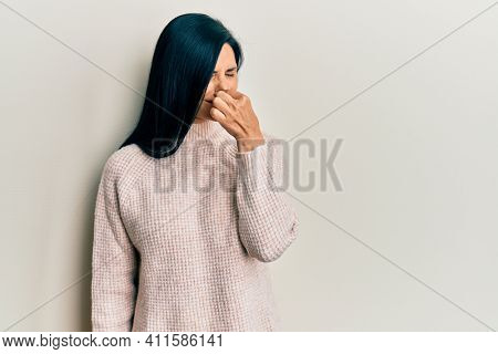 Young caucasian woman wearing casual winter sweater smelling something stinky and disgusting, intolerable smell, holding breath with fingers on nose. bad smell