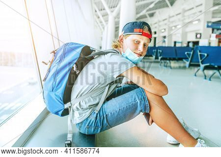 Portrait Of Lonely Teen Solo Traveler With A Backpack In Empty Airport Passenger Transfer Hall In Pr