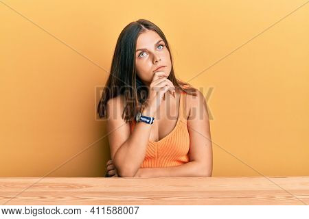 Young caucasian woman wearing casual clothes sitting on the table with hand on chin thinking about question, pensive expression. smiling with thoughtful face. doubt concept.