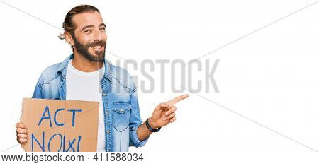 Attractive man with long hair and beard holding act now banner smiling happy pointing with hand and finger to the side