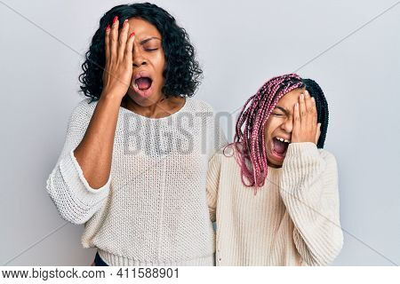Beautiful african american mother and daughter wearing casual clothes and hugging yawning tired covering half face, eye and mouth with hand. face hurts in pain.