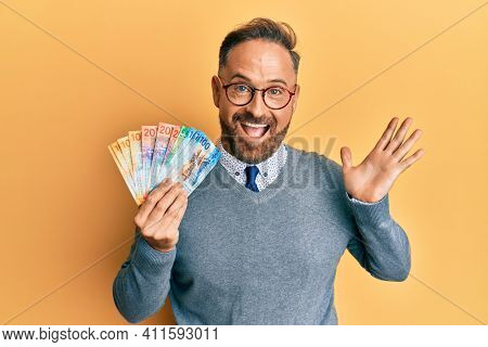 Handsome middle age man holding swiss franc banknotes celebrating achievement with happy smile and winner expression with raised hand