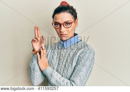 Young caucasian woman wearing casual clothes and glasses holding symbolic gun with hand gesture, playing killing shooting weapons, angry face