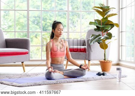 Asian Woman Practice Yoga Meditation Exercise At Home, Young Asia Female Sitting On Mat For Relaxed