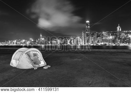 People Camping On Seaside Promenade Of Victoria Harbor In Hong Kong City At Night