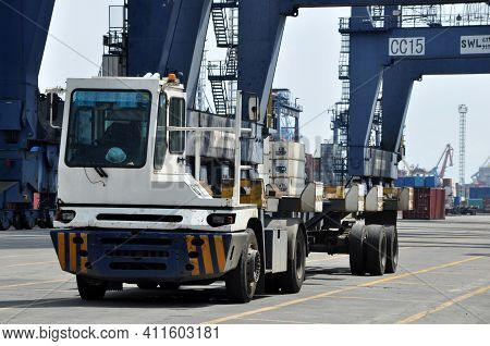 Jakarta, Indonesia - May 6, 2017: Container Trucks Passed Between Stacks Of Containers At The Port O