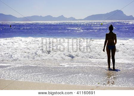 Girl on the beach looking to an island