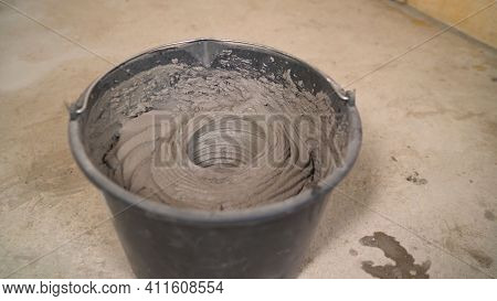 Man Is Mixing Grey Concrete And Prime In The Bucket. Mixed Grey Concrete And Prime In The Bucket - R