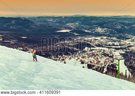 Mountain Slope. Snowboarder Rides Snowboard. Sunset Over Sheregesh Ski Resort. Siberia, Russia.