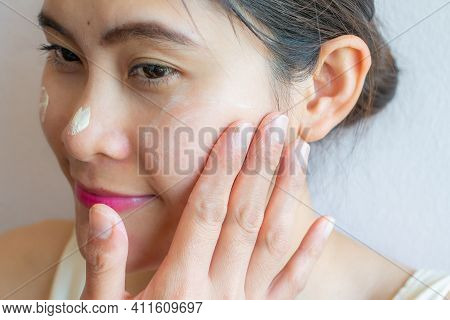 Close Up Of Asian Woman Marking And Applying Cream Concealer On Her Facial Skin. Concealer Is A Type
