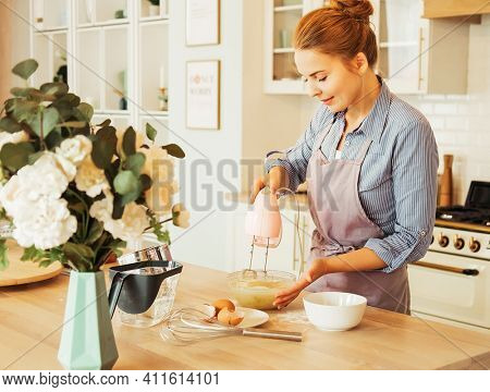 Lifestyle, cooking and freelance concept: Young woman baking a cake in the kitchen standing at the counter in her apron using a handheld mixer to whisk the fresh ingredients in a glass mixing bowl.