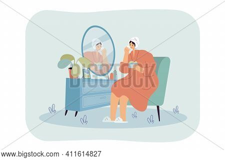 Young Woman Sitting In Front Of Mirror And Washing, Cleansing Or Moisturizing Her Face Skin In Morni