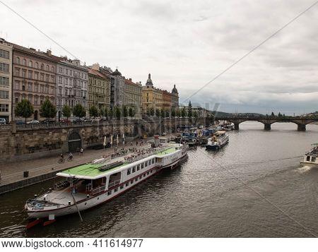 Ferryboats At Naplavka And Colorful Buildings At Rasinovo Embankment And Palackeho Bridge At Backgro