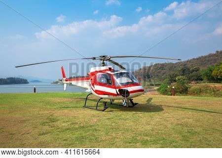 The Front Of The Red Helicopter Landed At The H Helicopter Landing Spot With Grass And River In The