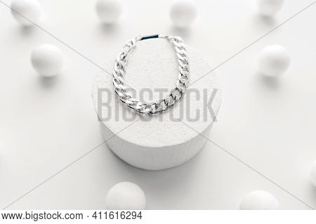 Imitation Jewelry, Silver Bijouterie Chain Bracelet On White Background. White Podium And Little Sph