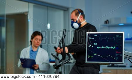 Team Of Medial Researchers Monitoring Vo2 Of Man Performance Sports Wearing Mask Running. Lab Scienc