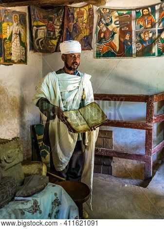 Yeha, Ethiopia - Feb 10, 2020: An Orthodox Priest Shows A Painted Holy Bible From The 14th Century I