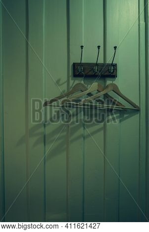 Brown Wooden Cloth Hanger With Shadow Hanging On Metal Hook On Wooden Wall Background. Empty Coat Ha