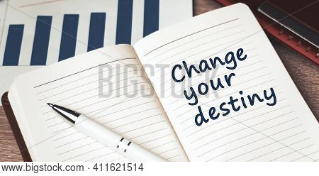 The Words Change Your Destiny Written On A White Notebook. Closeup Of A Personal Agenda
