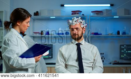 Researcher Neurologist Doctor Asking Mans Symptoms Taking Notes On Clipboard Before Brain Scan With