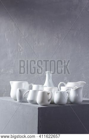 Empty milk jars or creamers dishes set. Kitchen dishware and tableware on grey cube near wall background texture