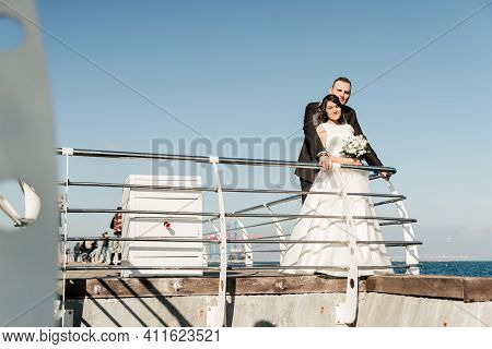 Wedding Couple On A Yacht. Groom With The Bride On The Background Of The Sky. The Newlyweds Stand Ne