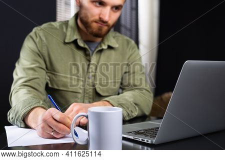 Working From Home, Casual Business Man Using Laptop Computer, Writing On Notebook With Cup Of Tea On