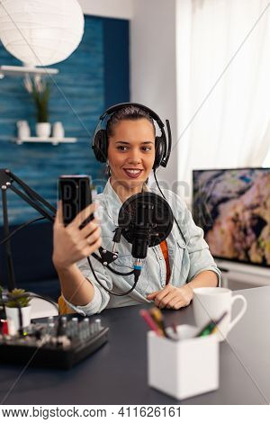 Portrait Of Blogger Woman Taking Selfie For Audience Using Smartphone Working In Podcast Home Studio