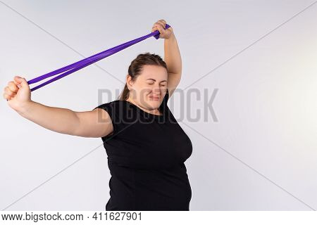 Healthy Woman Exercising With Resistance Band Against Gray Background. Plus Size, Overweight Woman I