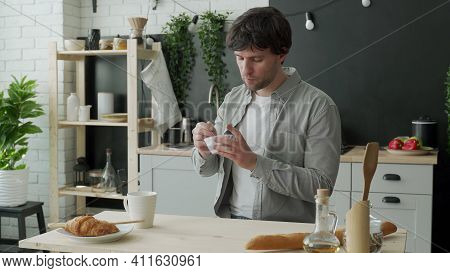 Young Man Eating Yogurt In The Kitchen At Home