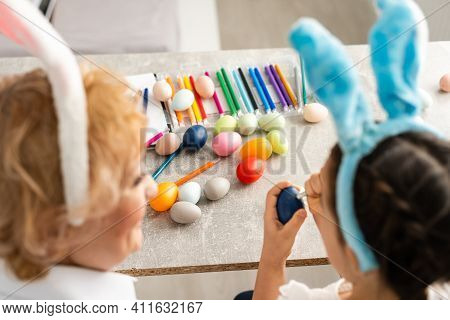 Happy Easter. A Grandmother And Her Granddaughter Painting Easter Eggs. Happy Family Preparing For E